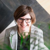 Krisztina Kun Headshot with short brown hair and glasses in grey blazer