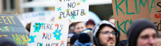 "Photo by Markus Spiske on Unsplash showing environmental rally with signs ""there's no planet B"""